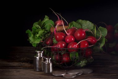Fresh wet radishes in a basket on the an old wooden table. Village style. Dark key photo.