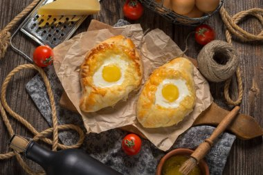 Adzharian khachapuri with egg on the wooden table. Top view.
