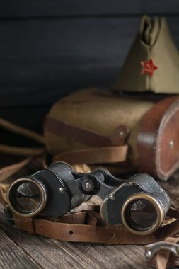 Military binoculars and a cap on a dark background, vintage style