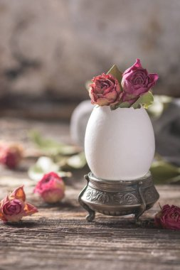 Easter decoration. Dry roses buds in the egg-shell. Rustic style. Close view. Selective focus.