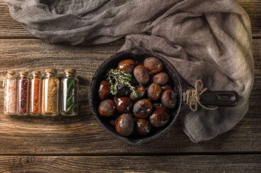 Chestnuts. Roasted edible chestnuts served in cast iron skillet on dark wooden table.