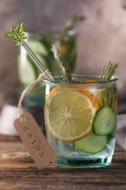 Detox fruit infused water. Refreshing summer homemade cocktail, selective focus. Wooden rustic background. Cold and refreshing detox water with lemon and cucumber.