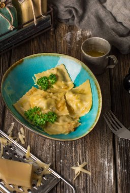 Italian ravioli pasta with mushrooms and ricotta on wooden rustic background. Top view