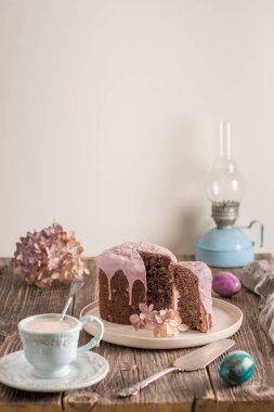 Easter composition with orthodox sweet bread, kulich and eggs on light background. Easter holidays breakfast concept with copy space.