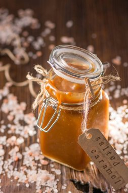 Homemade salted caramel sauce in the glass jar. Selective focus, space for text