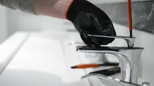 Instalatér opraví kohoutek ve veřejné toalety