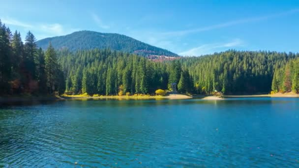 Autumn Mountain Lake with Colorful Trees in the Forest and Fallen Leaves on the Water. Timelapse.