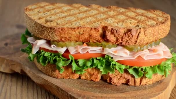 rotation of tasty turkey sandwich with tomato, salad and cucumber, on wooden background