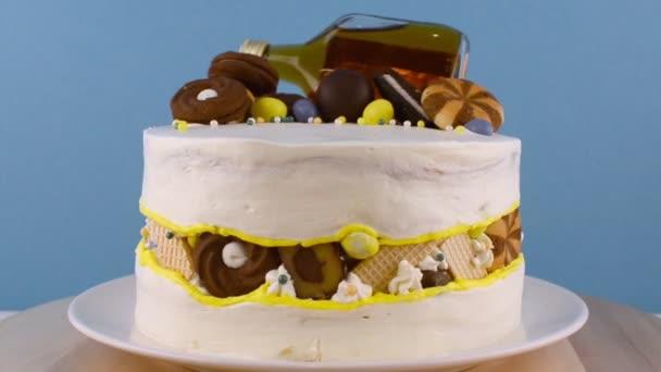 vicces torta forgatása egy üveg alkohollal, cukorkával és sütikkel
