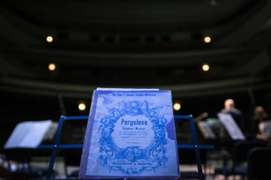 Old music book with notes of the cantata of Stabat Mater of the Italian composer of Pergolese on the stage of the Kharkiv Opera Theatre. Ukraine, Kharkiv, KHNATOB, on April 25, 2018