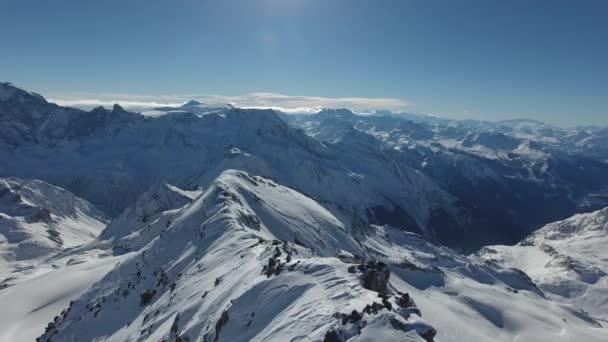 Krásný filmový dron záběr zasněžených hor ve francouzských Alpách. Úžasná krajina slunečný den modrá obloha.