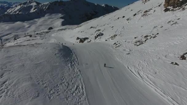 Luftaufnahme nach einem Skifahrer, der einen Berg in den französischen Alpen hinunterfährt, la plagne. Sonniger Tag