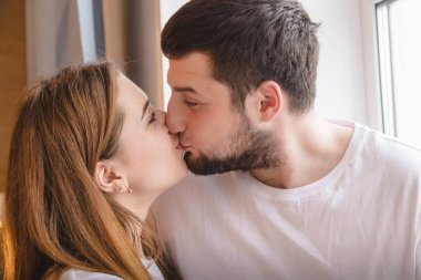 Lovely couple have fun and relax at home near window. Lifestyle concept