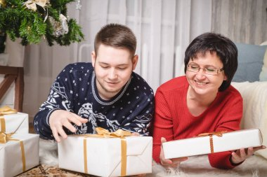 Mother and adult son in the room decorated for Christmas and New Year
