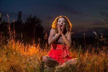Elf girl in a black top and red skirt in grass of field in the evening. Model with white face during a photo shoot on nature at night time