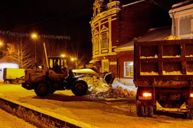 Kirov, Russia - December, 28: Tractor and truck cleaning snow at night on the streets of Kirov in Russia
