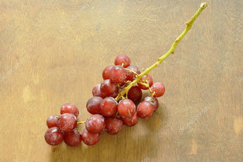 fresh red grape on wooden board