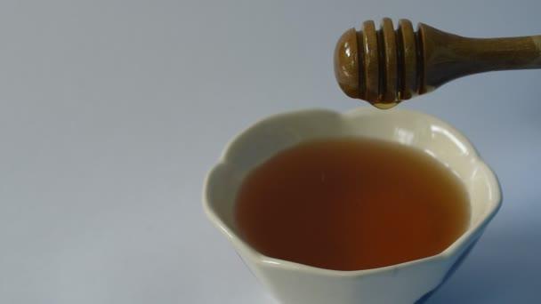 Med na dřevěné naběračky na šálek v bílém pozadí