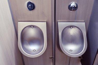 New modern metal urinals in public toilet