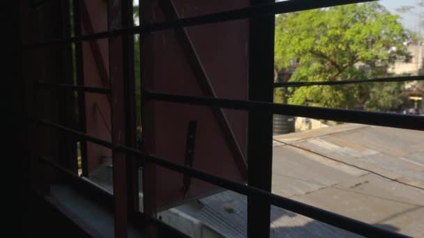 Slow pan up of metal window frame with metal bars