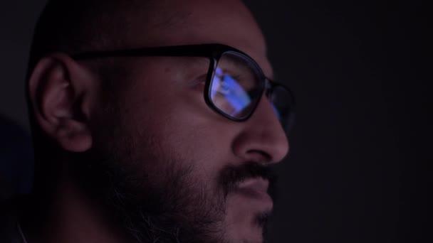 Ázsiai férfi néz Monitor Tükröződése Számítógépes képernyők látott szemüveg a sötét szobában. Lezárva