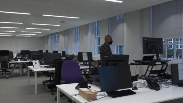 Dospělí UK Asian Male Walking Towards Standing Desk In Empty Office Wearing Face Mask. Uzamčeno