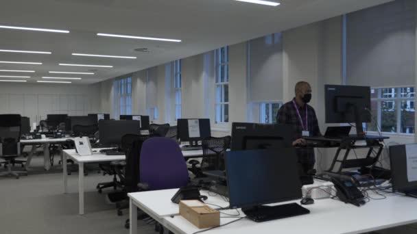 Erwachsene Männer, die im leeren Büro arbeiten, tragen während der Sperrung eine Gesichtsmaske. Abgeriegelt