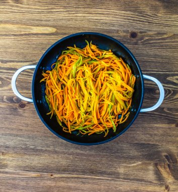 thinly cut thin strips of carrots. fried and stewed carrot spaghetti in a pan on a wooden table