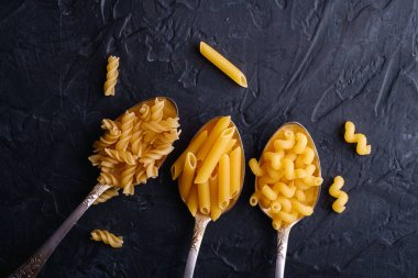 Three cutlery spoons with variety of uncooked golden wheat pasta on dark black textured background, top view