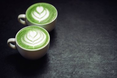 Two cups of coffee on black rustic background