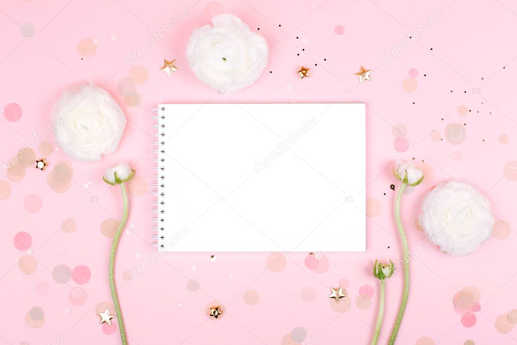 Notebook with flowers on pink pastel background