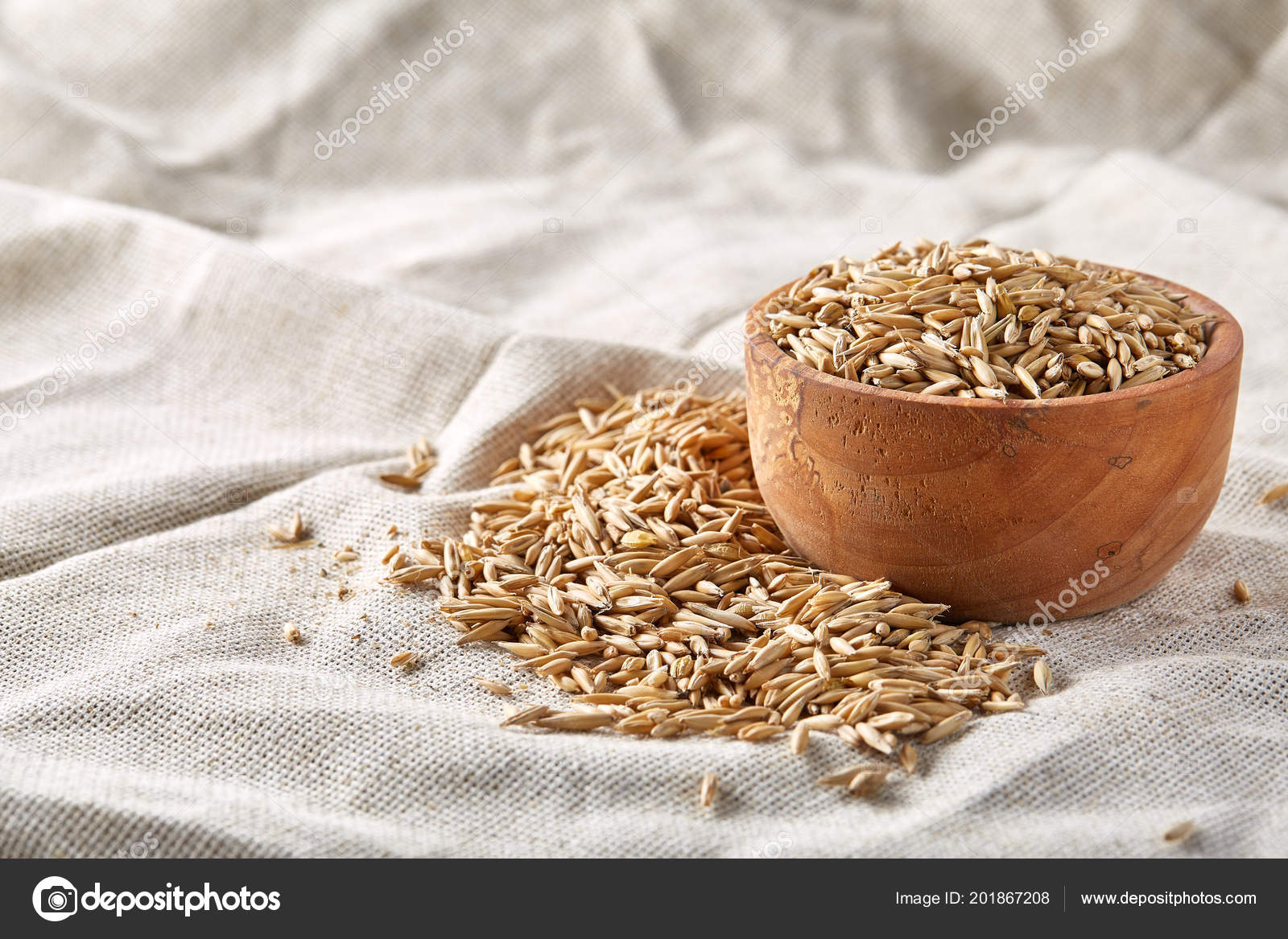 Oat groats or oat spike in wooden plate on homespun tablecloth
