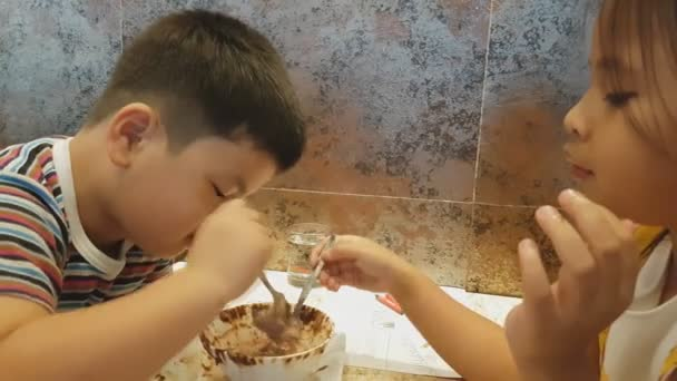 Asian cute Kids eating ice cream by glass cup in restaurant,