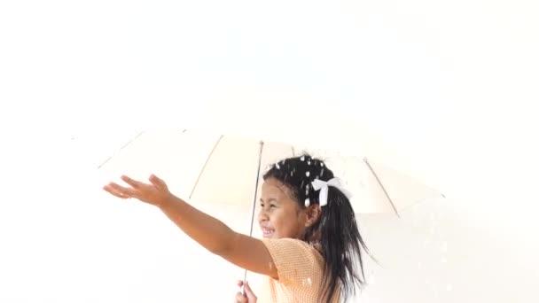 das Mädchen streckte die Hand aus, um den fallenden Regen aufzufangen und hielt den Regenschirm in ihren Händen.