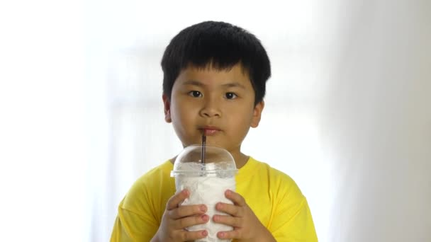 kleine süße Junge trinken Wasser und Milch durch Rohr auf weißem Hintergrund,