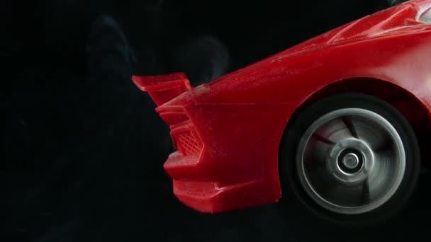 Červené auto kolo kouř se točí na černém pozadí,
