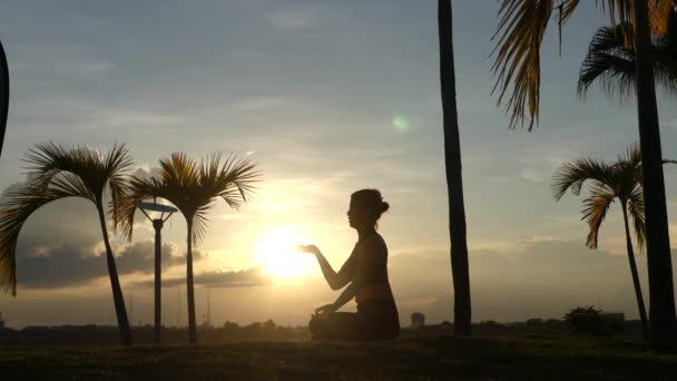 Žena meditací se drží ruku na slunce pozadí