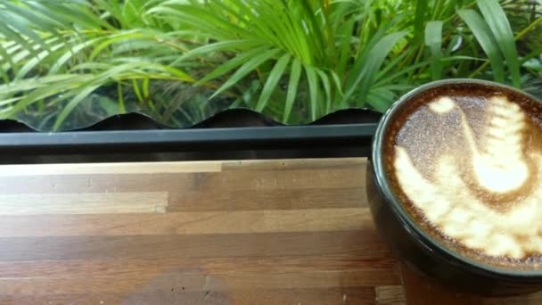 Black glass with latte art on the wood table