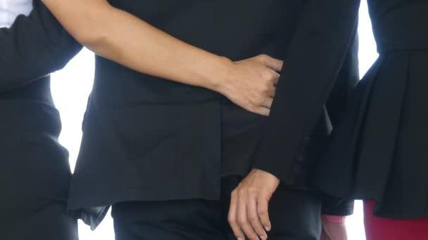 Gli uomini daffari femminili si tengono per mano dietro gli uomini daffari maschi