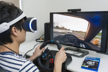 Playing racing video game with VR headset at home