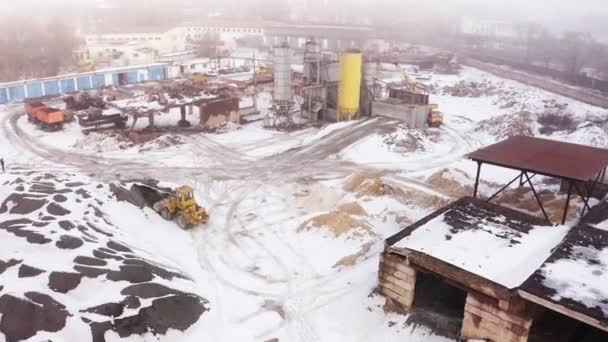 MARIUPOL, UKRAINE - January 9, 2019 : Concrete-mixing plant . Tractor transports cargo. Winter