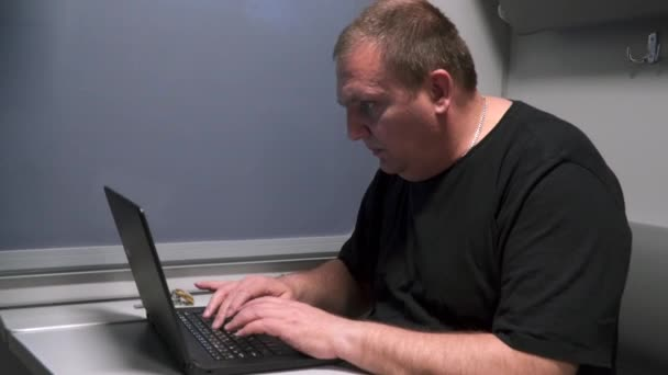 A man near the window of a moving train works with a laptop.