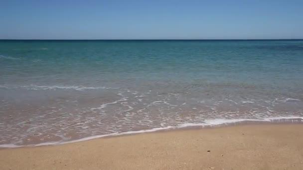 vlny líbající písek na pobřeží