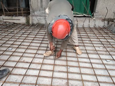 KUALA LUMPUR, MALAYSIA -MARCH 29, 2010: Construction workers fabricating steel reinforcement bar to form reinforcement concrete at the construction site. They tied it together using the tiny wires