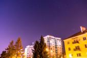 Obytné budovy v noci s narůžovělou oblohou plnou hvězd na Slovensku.