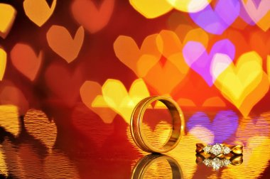 Two golden wedding rings with heart bokeh on background.Concept of love, Valentine, soul mate, destiny.