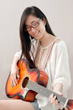 Smiling asian beautiful girl wearing eyeglasses and playing guitar in the music room, leisure concept.