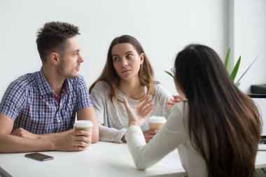 Serious concerned couple looking at each other not liking what real estate agent or advisor telling, thinking about offer, making negative decision. Bad suggestion make customers unhappy, dissatisfied stock vector