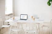 Jednací stůl s notebooky a kávu v pokoji prázdnou kancelář