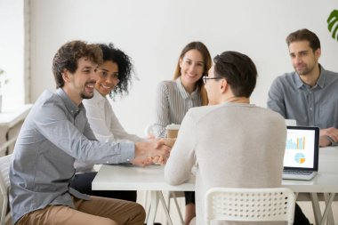 Two smiling businessmen shaking hands at multiracial group meeti